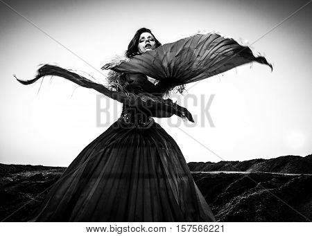Black-white fine art portrait of attractive romantic woman at fairy tale dry field.