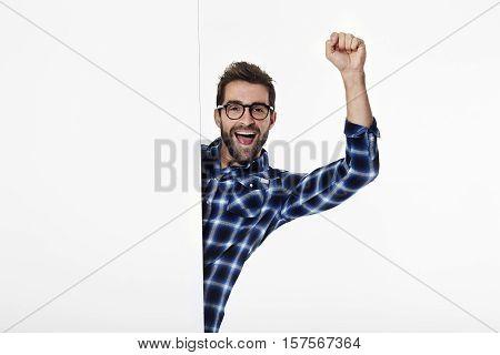 Cheering man in checked shirt in white studio