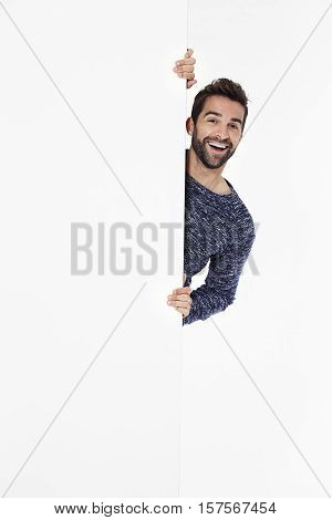 Man laughing behind white wall portrait white background