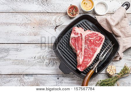 T-bone Steak on frying grill pan with meat fork, oil and seasoning on white wooden background , top view