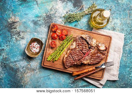 Grilled t-bone or porterhouse steak seasoned with thyme on a wooden board with tomatoes, asparagus and seasonings, top view