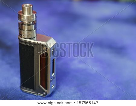 Modern electronic mod vaping device. New vaporizer e-cig gadget dna. Blue background. Space for text.