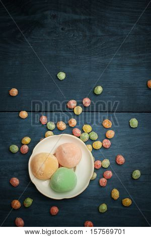 Mochi Rice Cakes In White Plate With Colorful Fruit Candy Drops At Wooden Background