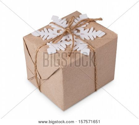 Gift box or mail parcel, post delivery wrapped with kraft paper and twine rope and decorated with snowflake isolated on white background. Craft present for christmas, winter holidays concept.