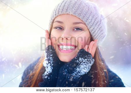 Winter girl portrait. Beauty Joyful Teenage Model Girl touching her face skin and laughing, having fun in winter park. Beautiful young woman laughing outdoors. Enjoying nature.