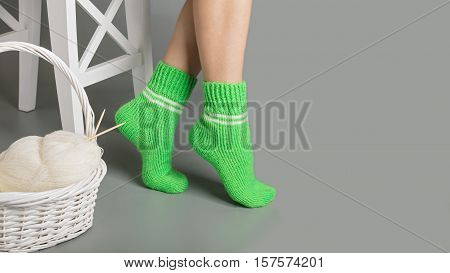 Female legs in green knitted socks near the basket with yarn and knitting.