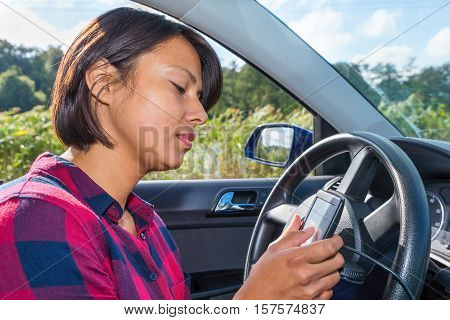 European woman operates digital route planner in car
