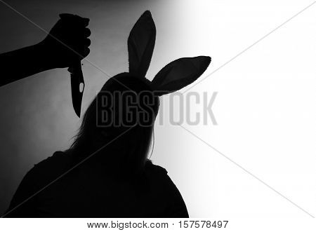 Silhouette of young girl with rabbit ears and hand with knife. Children abuse, domestic violence and neglected child concept. Black and white photography. Picture with space for your text.