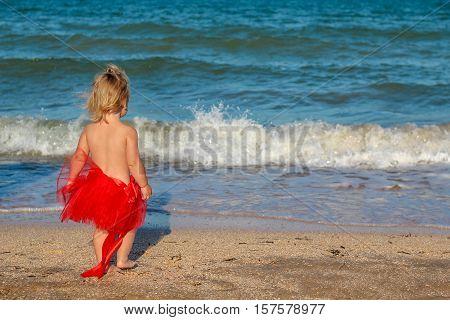 Christmas Baby Girl Playing On The Beach Near The Sea
