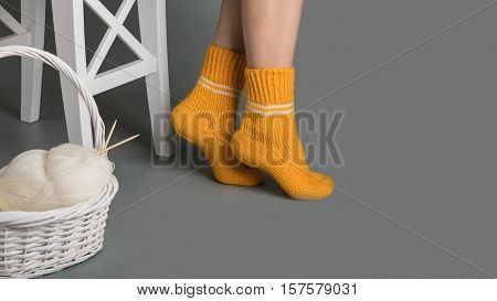 Female legs in yellow knitted socks near the basket with yarn and knitting.