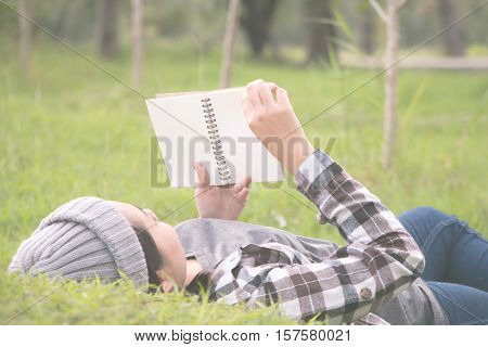woman laying and lookin book in a park on sumer day