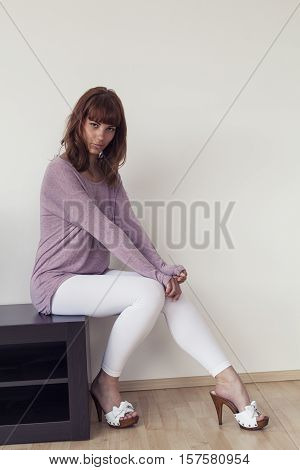 Pretty brunette girl posing with purple shirt white leggings and wooden high heels looking at the camera space for copy text