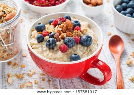 Oatmeal porridge with fresh blueberries, raspberries, muesli and almonds in red bowl on white table. Healthy breakfast, healthy eating, vegan food concept. Colorful breakfast for kids