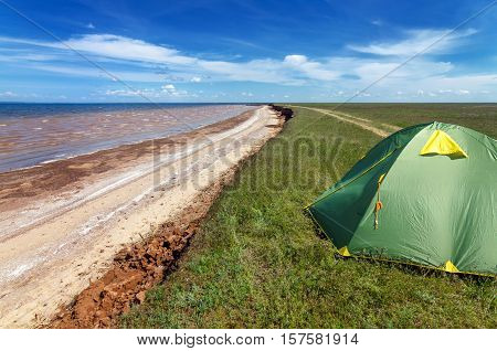 A touristic green tent set up in astrakhan steppe under beautiful sky shoot in May. Spring is beautiful time. Steppe are green and covered by emerald grass. Panorama of steppe near salt lake Baskunchak Russia