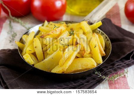 Roasted fried buttery potatoes with thyme in pan