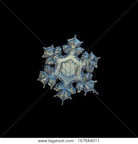 Snowflake isolated on black background. This is closeup image of real snow crystal: medium size stellar dendrite with six short arms and big, empty central hexagon.