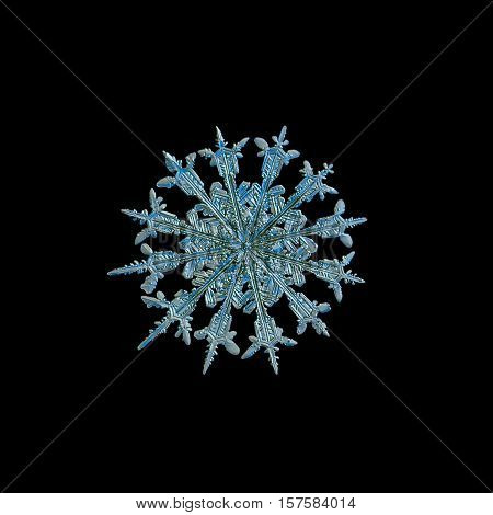 Snowflake isolated on black background. This is macro photo of real snow crystal: rare snowflake with twelve symmetrical arms and complex inner structure.