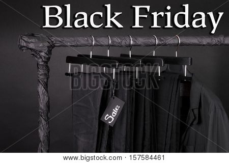 A Lot Of Black Pants Jeans And Jacket Hanging On Clothes Rack.  Background. Sale Sign.  Friday. Clos
