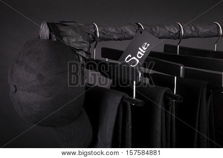 Sale Sign. Black Cap And Pant, Jeans Hanging On Clothes Rack   Background.   Friday.  Close Up.