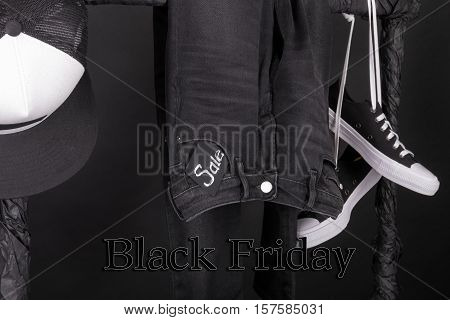 Black Friday. Sale Sign.  And White Snaekers, Cap  Pant, Jeans Hanging On Clothes Rack   Background.