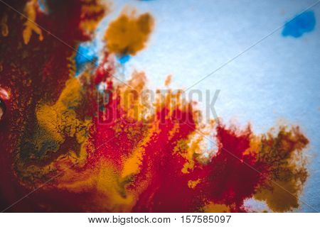 divorces and paint drips red, orange, yellow, blue blurred abstract background on a white paper background plane surface close-up macro with filter toning effect