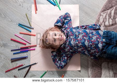 Child Lying On The Floor  Paper Looking At The Camera Near Crayons. Little Girl Painting, Drawing. T