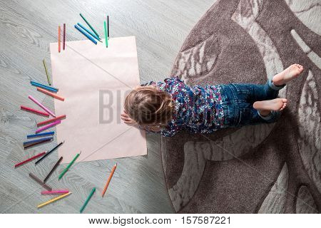 Little Girl Painting, Drawing. Child Lying On The Floor Near Crayons. Top View. Creativity Concept.