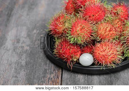 rambutan sweet fruit fresh in plate on wood background : Select focus with shallow depth of field.