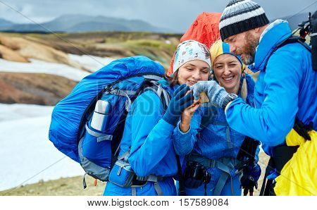 couple friends hikers un the Islandic mountains. two woman and one man photographer taking picture on the rhyolite mountains background in Iceland. people looking at the smartphone and laughs