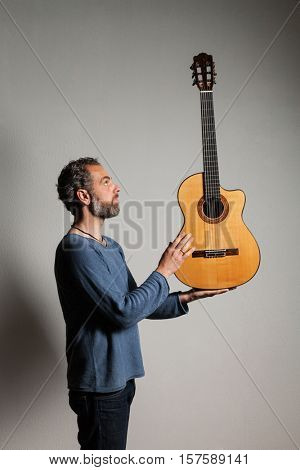 interior, portrait of man grizzled with classical guitar