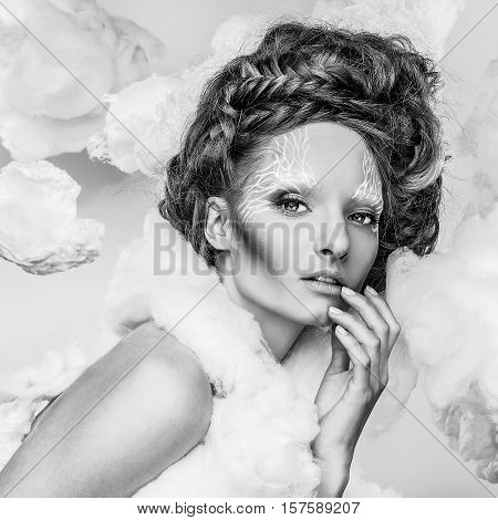 Romantic beauty with magnificent hair wandering in clouds. Fine art black-white studio fashion portrait.