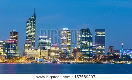 PERTH WESTERN AUSTRALIA - APRIL 7 2016: Dusk falls over the city of Perth, the capital of Western Australia. The Swan River can be seen in the foreground.