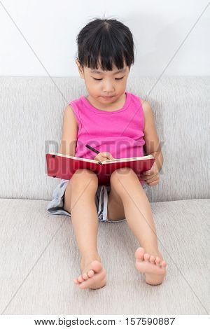 Asian Chinese Little Girl Sitting On The Sofa Writting Book