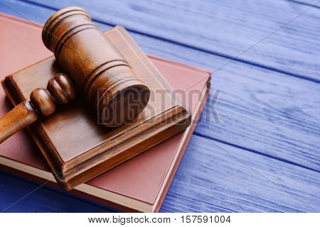 Gavel with sound block and book on wooden background
