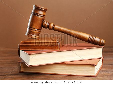 Judge's gavel and books on brown background