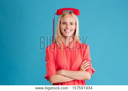 Portrait of a smiling cheerful blonde woman standing with red telephone tube on her head isolated on a blue background