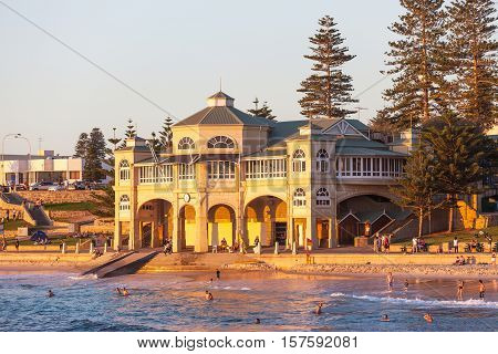 PERTH AUSTRALIA - APRIL 25 2011: Swimmers relaxing and bathing at sunset in front of the iconic old pavillion at Cottesloe Beach in Perth, Western Australia.