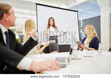 Woman in a meeting giving a lecture during a presentation in a conference room
