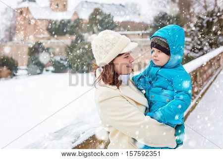 Little toddler kid boy and young mother playing with snow in winter park. Happy family of two in winter clothes having fun together. Woman holding and hugging cute adorable son on arm, outdoors.