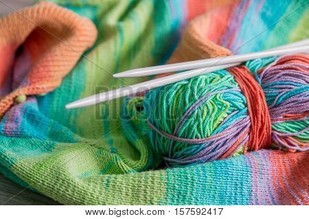 Knitting. Knitted Sweater. Multicolor Ball Of Yarn With Needles Near The Handmade Products. Close Up