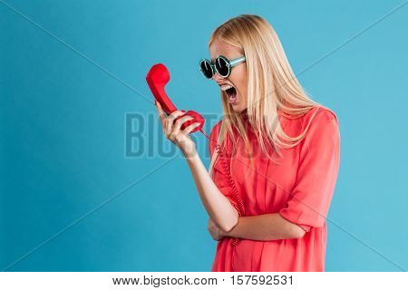 Upset furious woman in sunglasses screaming on phone tube isolated on a blue background