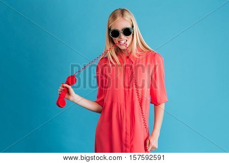 Portrait of a stylish blonde girl in sunglasses with telephone wire in mouth isolated on a blue background