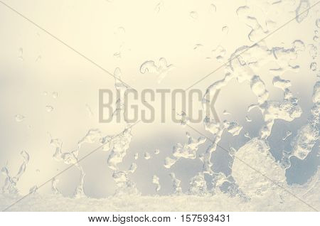 Ice water drops on winter glass. Frost patterns on window. Frosty natural pattern on winter window. Ice on a window background texture. Light blue frozen window glass background.