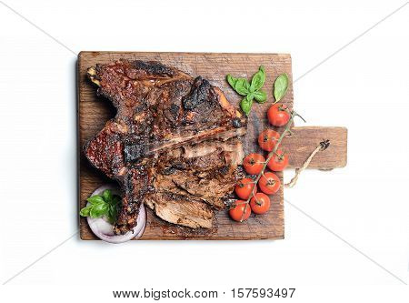 large grilled steak on a cutting board on a white background
