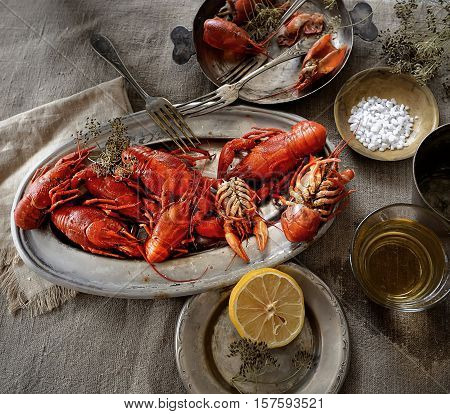 boiled crawfish in a metal dish, lemon, dill and beer on a linen cloth