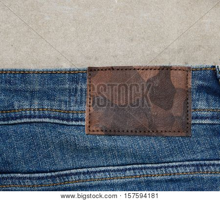 jeans pants with back pocket and brown leather tag-gray background