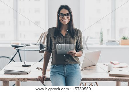 Confident and successful. Confident young woman in smart casual wear holding digital tablet and smiling while standing near her working place