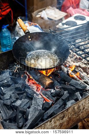 Old Chinese Wok Pan With Boiling Oil On A Fire