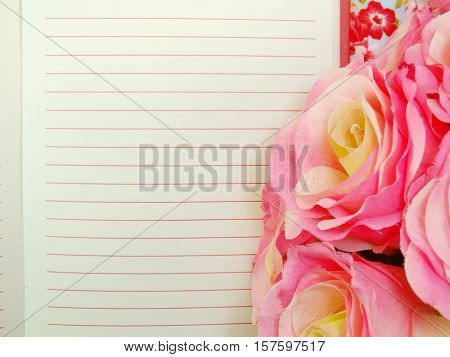 The Open Notebook Paper With Red Lines And Artificial Roses Flower