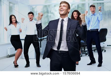 victory in business. jubilant businessman and business team on o